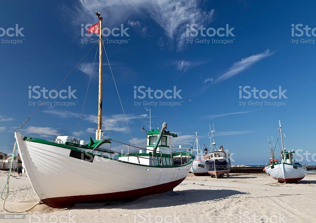 Fishing ship on sandy beach stock photo