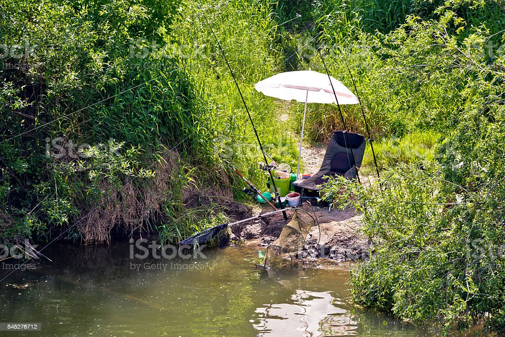 Fishing spot and gear in green landscape stock photo