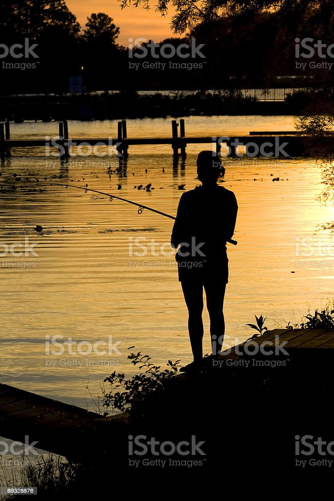 Fishing sunset with woman silhouette royalty-free stock photo