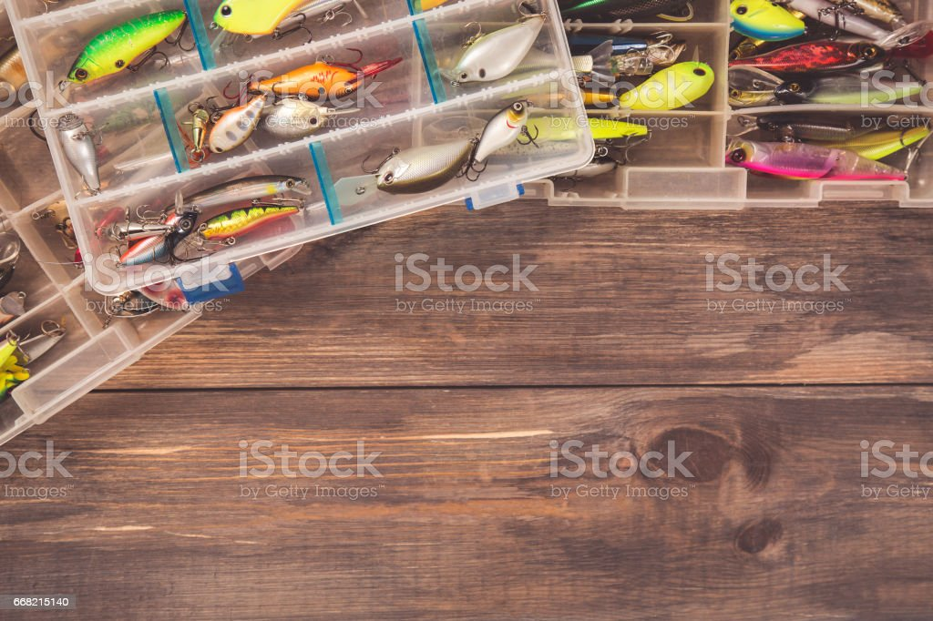 Fishing tackle boxes on wooden background with free space. Top view stock photo