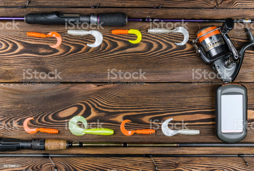 Fishing tackle - fishing spinning, fishing line, hooks, navigator and reel on wooden background stock photo