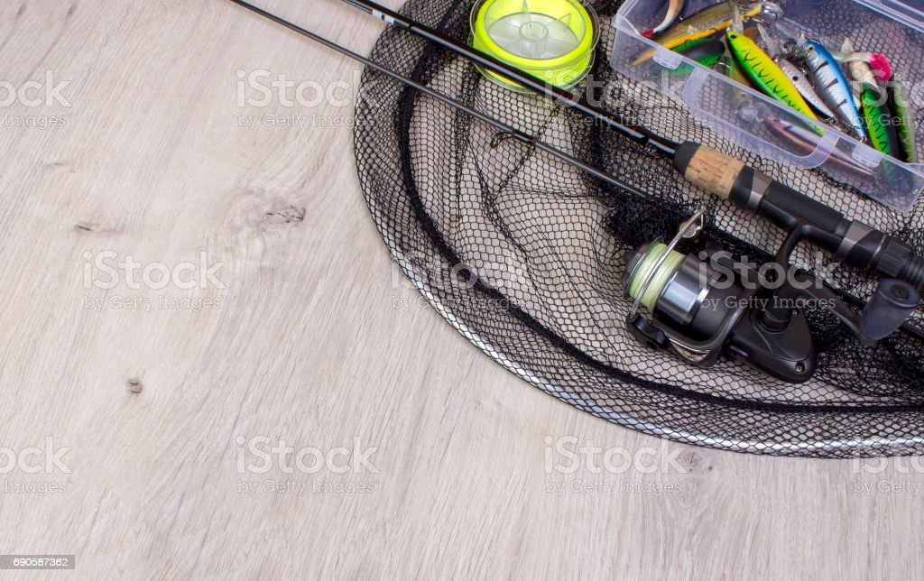 Fishing tackle - fishing spinning, hooks and lures on wooden background. stock photo