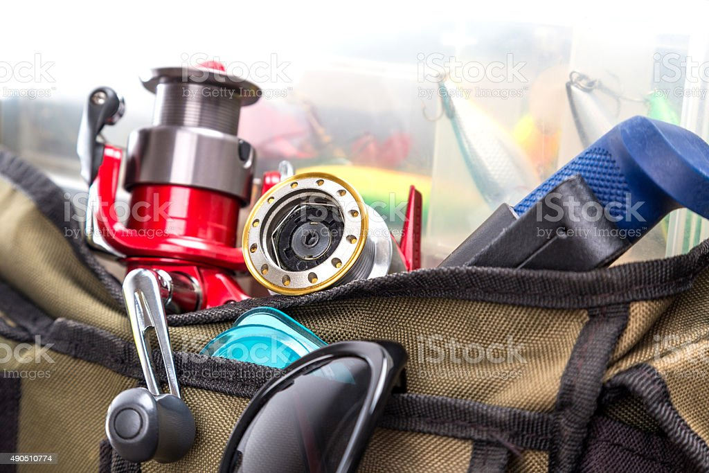 fishing tackles and lures in open handbag stock photo