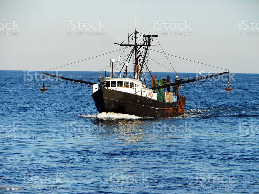 Fishing trawler boat sailing on calm blue ocean royalty-free stock photo
