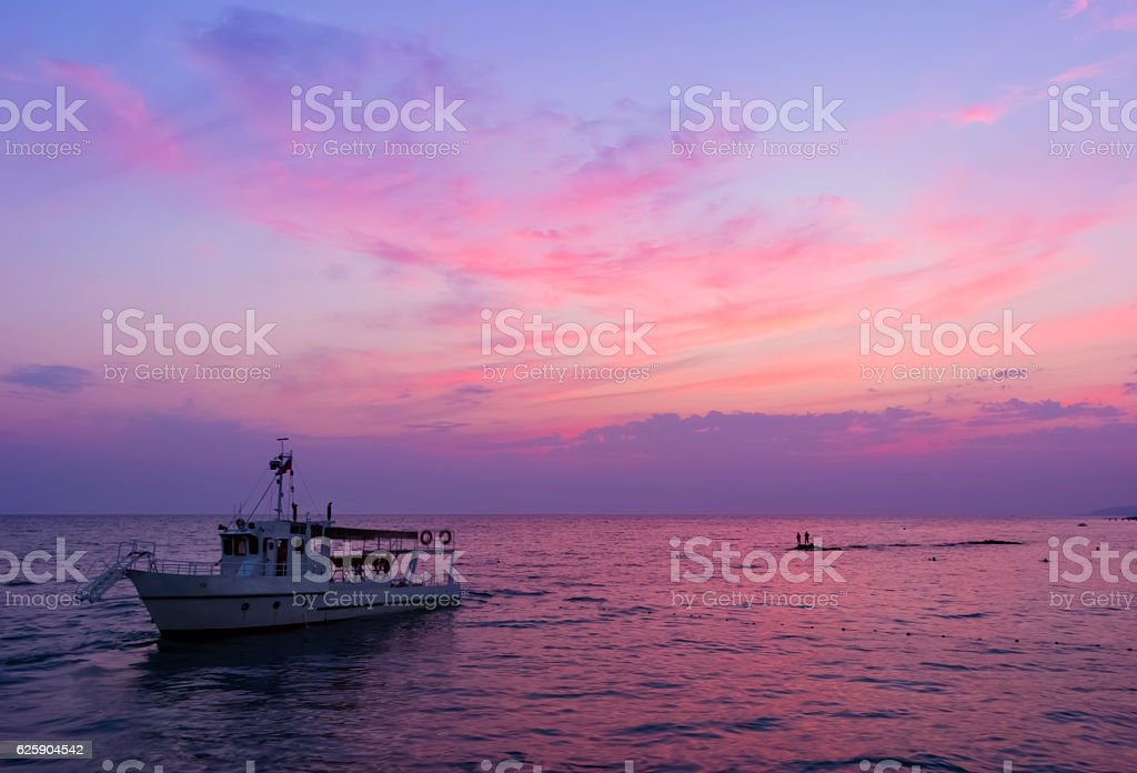 Fishing trawler on the water and dramatic clouds at sunrise stock photo