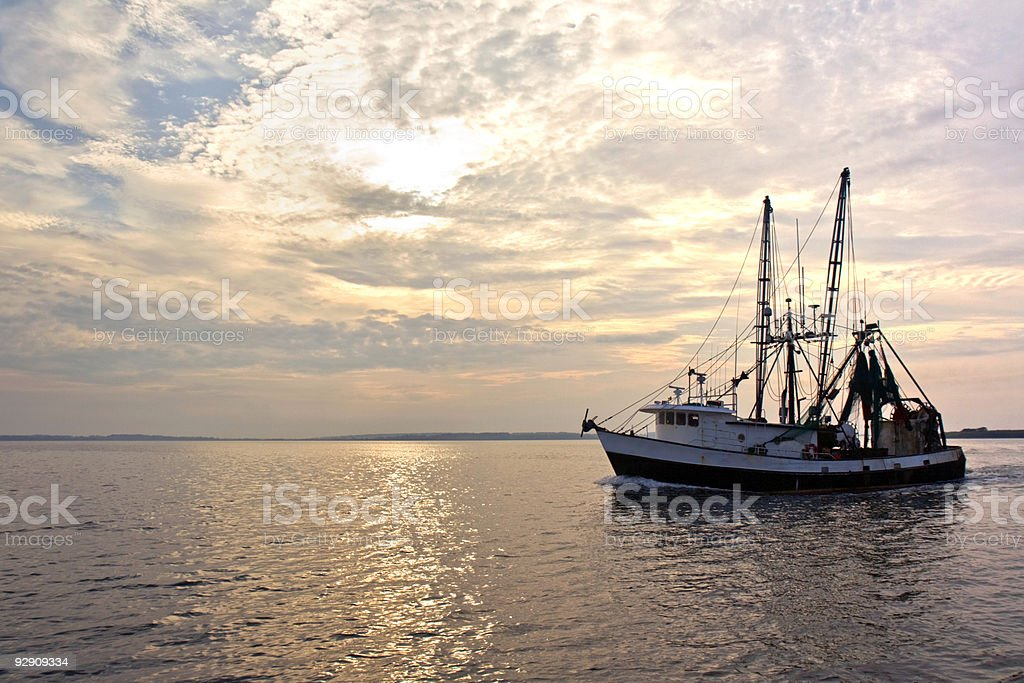 Fishing trawler on the water at sunrise stock photo