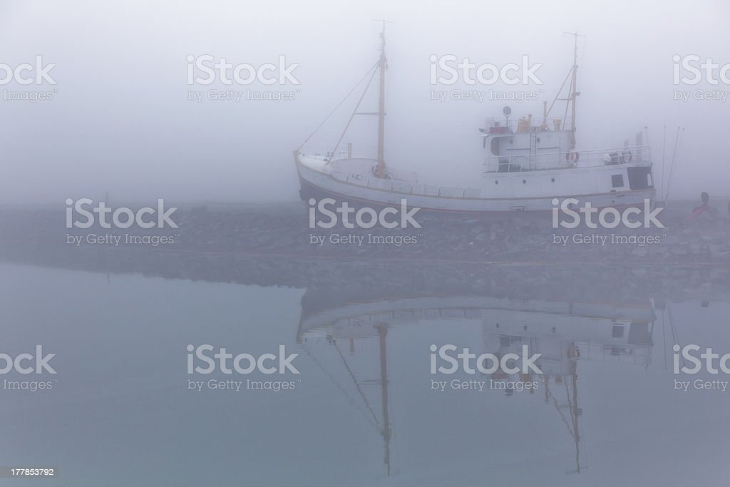 Fishing vessel in a foggy misty morning royalty-free stock photo