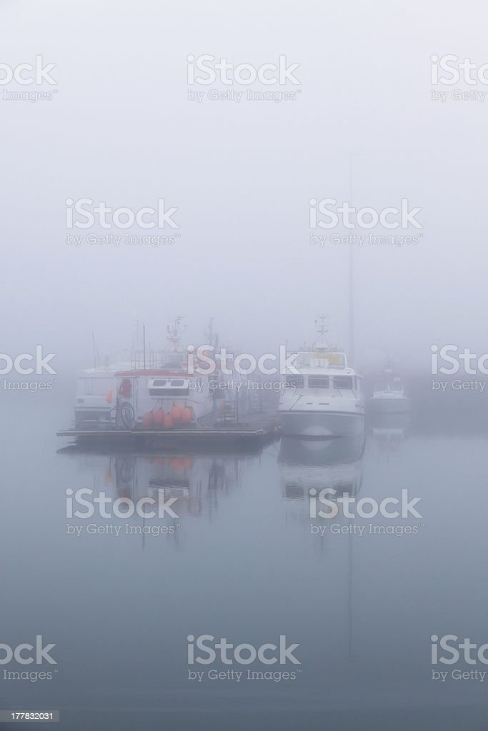 Fishing vessels in a foggy misty morning at Harbor royalty-free stock photo