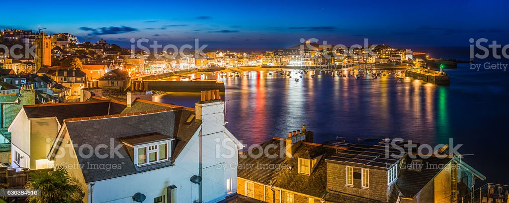 Fishing village cottages illuminated tranquil ocean harbour St Ives Cornwall stock photo
