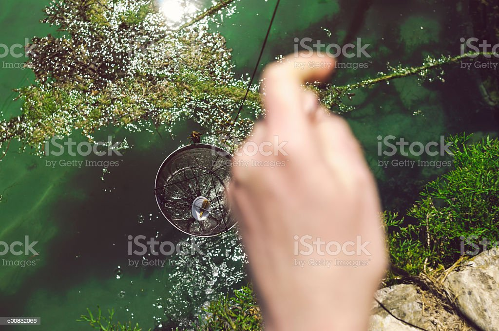 fishing with crab net in cornwall stock photo