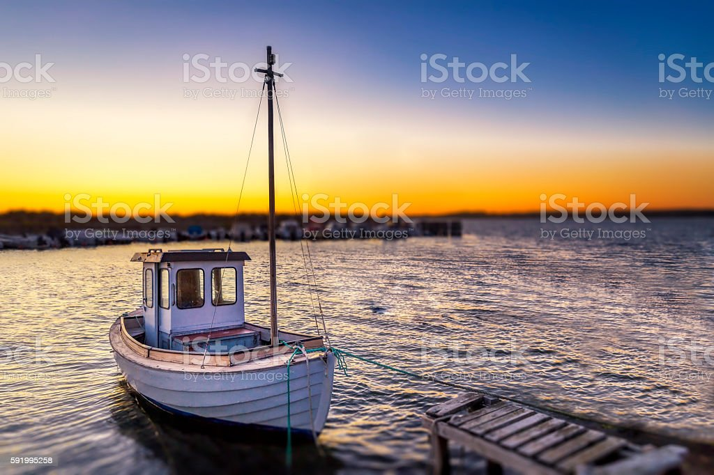 Fishingboat during sunset, tied by a small jetty stock photo