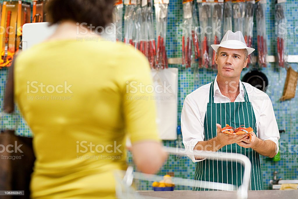 Fishmonger and customer in supermarket stock photo