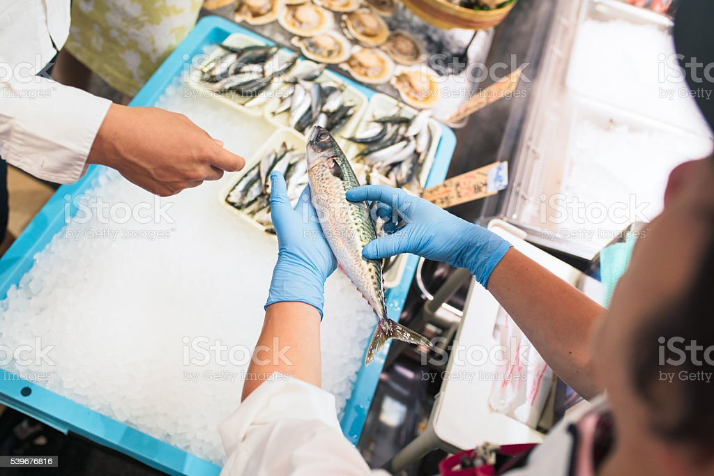 Fishmonger explaining to customers about fish stock photo