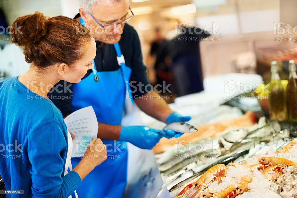 Fishmonger helping a customer stock photo