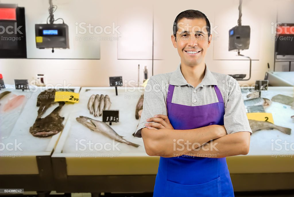 fishmonger in fish shop wearing black apron stock photo