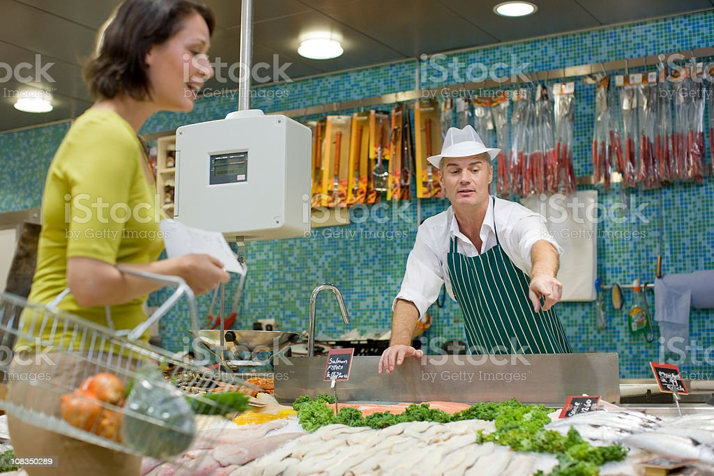 Fishmonger talking to customer in supermarket stock photo
