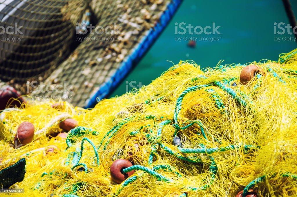 Fishnet lying near fishing boat stock photo
