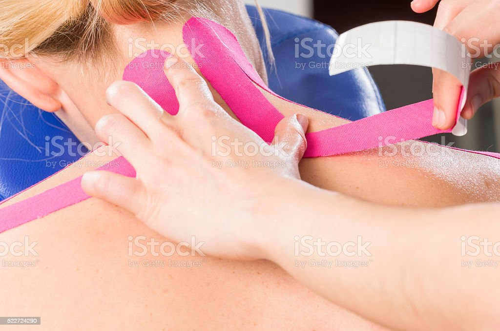 Fisiotheraphist/doctor applying cervical kinesiotape. stock photo