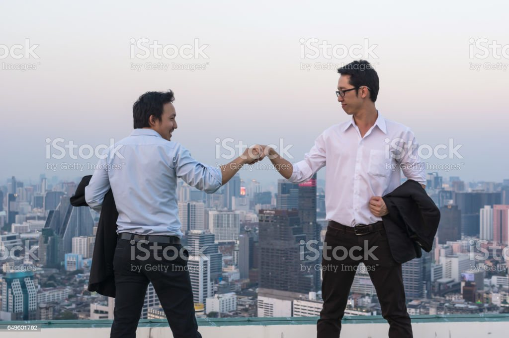 Fist Bumping Corporate Colleagues Teamwork between professional Couple businessman over the cityscape background at evening time, Business success concept stock photo