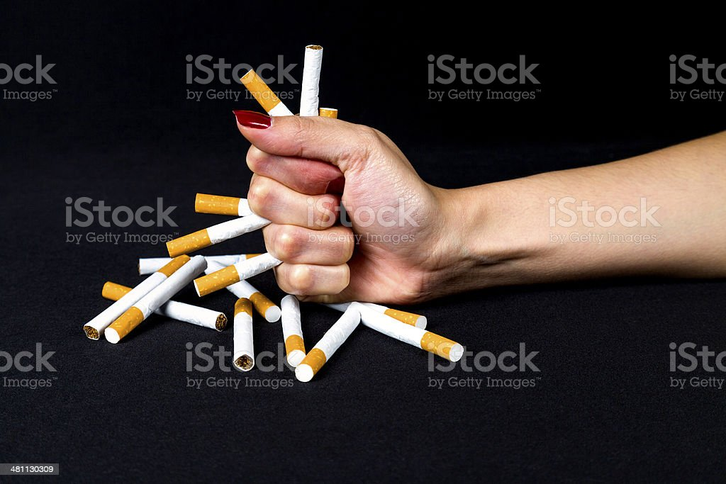 Fist hitting table with ciggarettes for quitting smoking stock photo