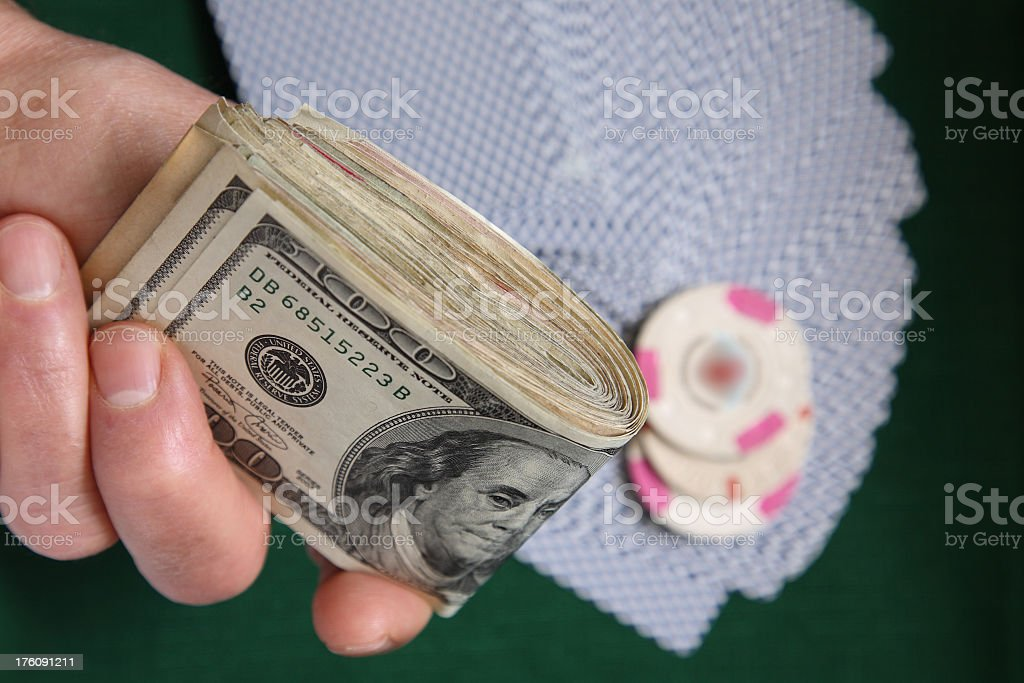 Fist of cash ready to gamble over cards and chips royalty-free stock photo