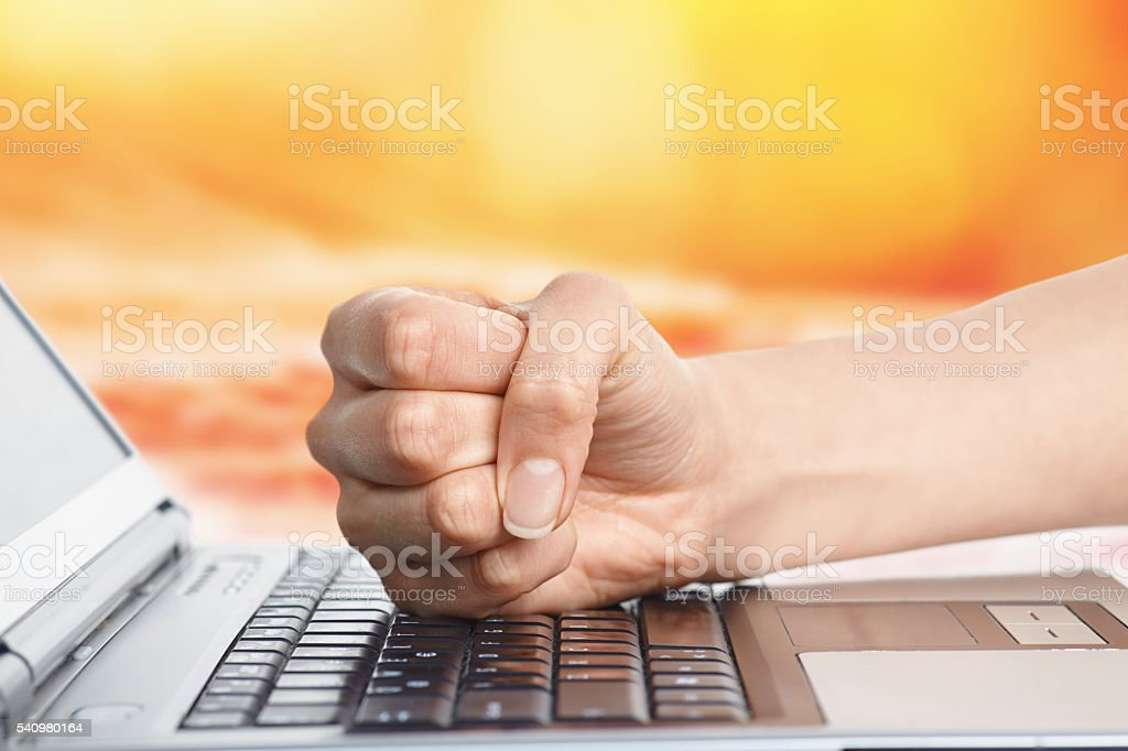 Fist on computer keyboard stock photo