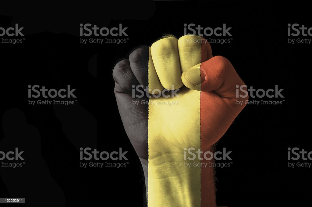 Fist painted in colors of belgium flag stock photo