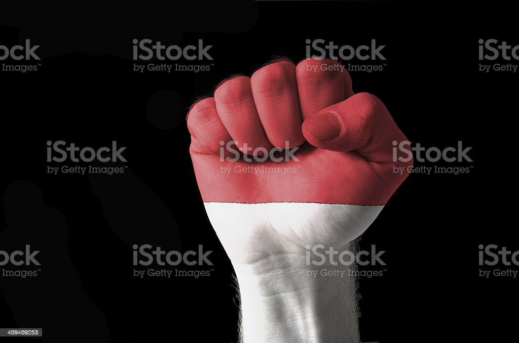 Fist painted in colors of indonesia flag stock photo