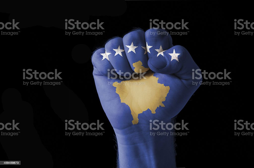 Fist painted in colors of kosovo flag stock photo