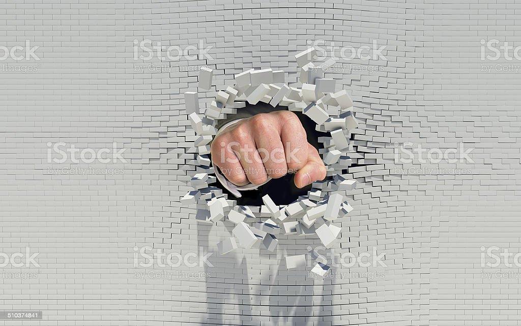 Fist punching through a brick wall stock photo