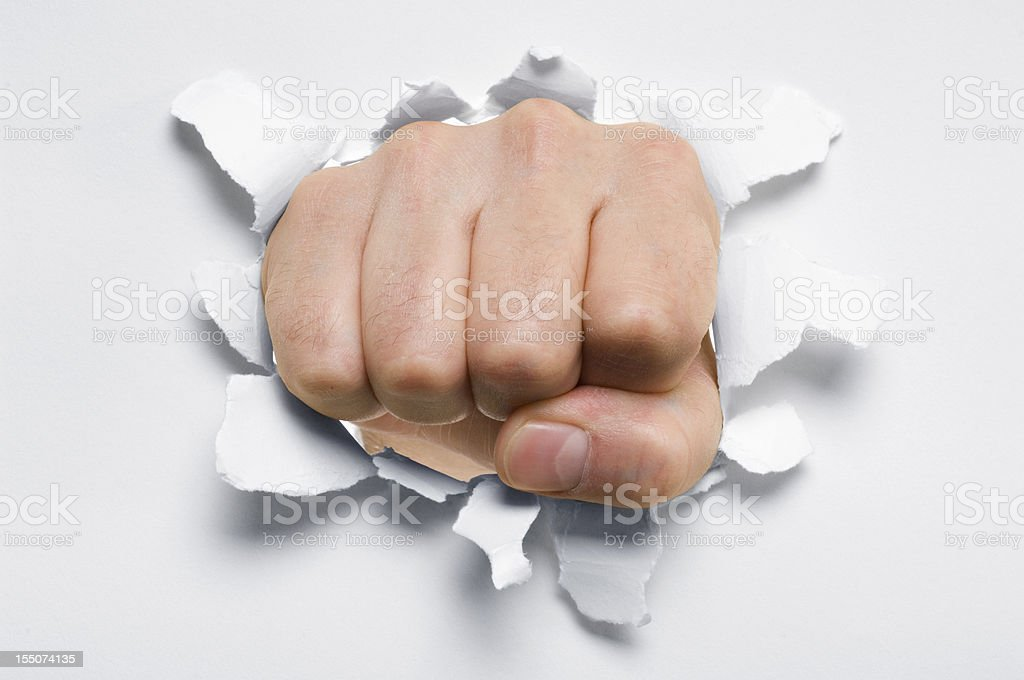 Fist punching through a ripped hole in a paper stock photo