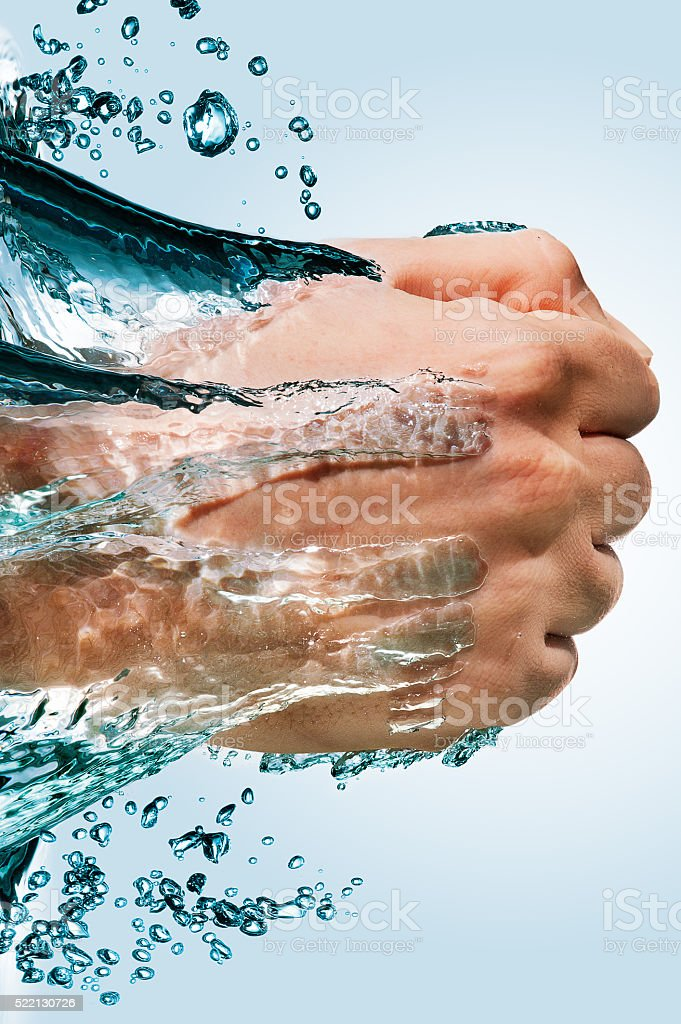 Fist through the water stock photo