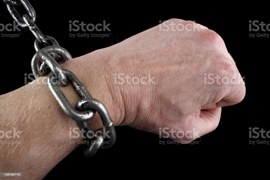 Fisted hand in shackles royalty-free stock photo