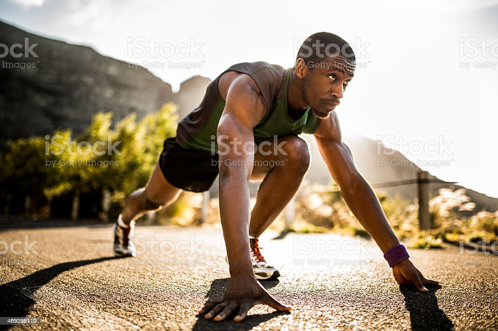 Fit African American athlete in a starting position stock photo