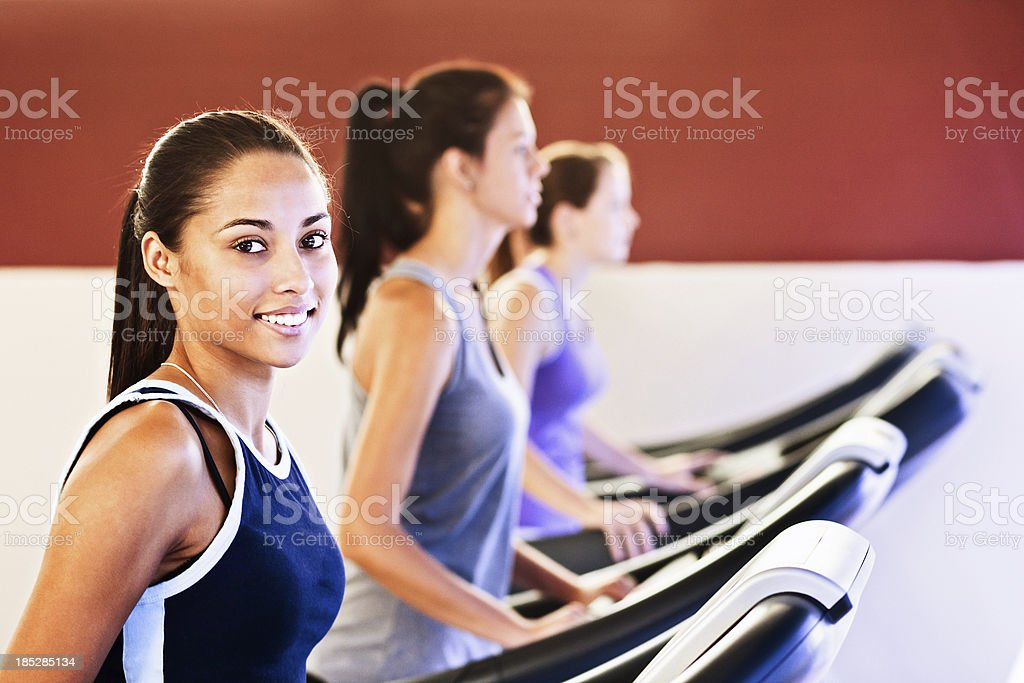 Fit and happy about it: smiling young woman uses treadmill stock photo
