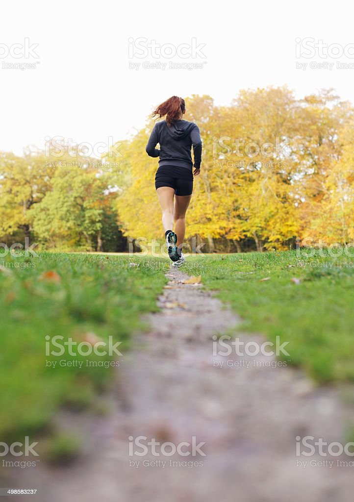 Fit and healthy female athlete running in park stock photo