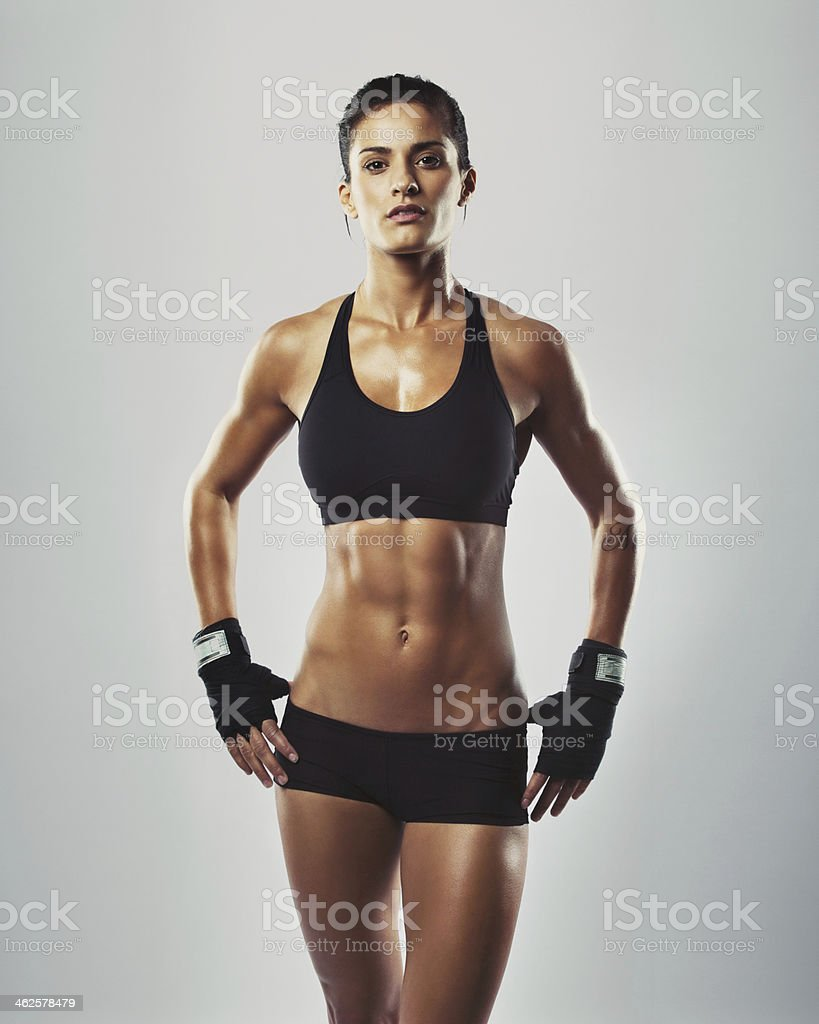 Fit and sexy young woman posing in grey background stock photo