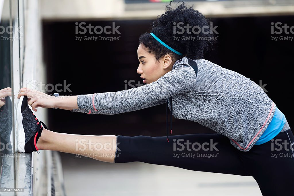 Fit and sporty young woman doing stretching in city. stock photo