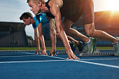 Fit athlete running race in athletics racetrack