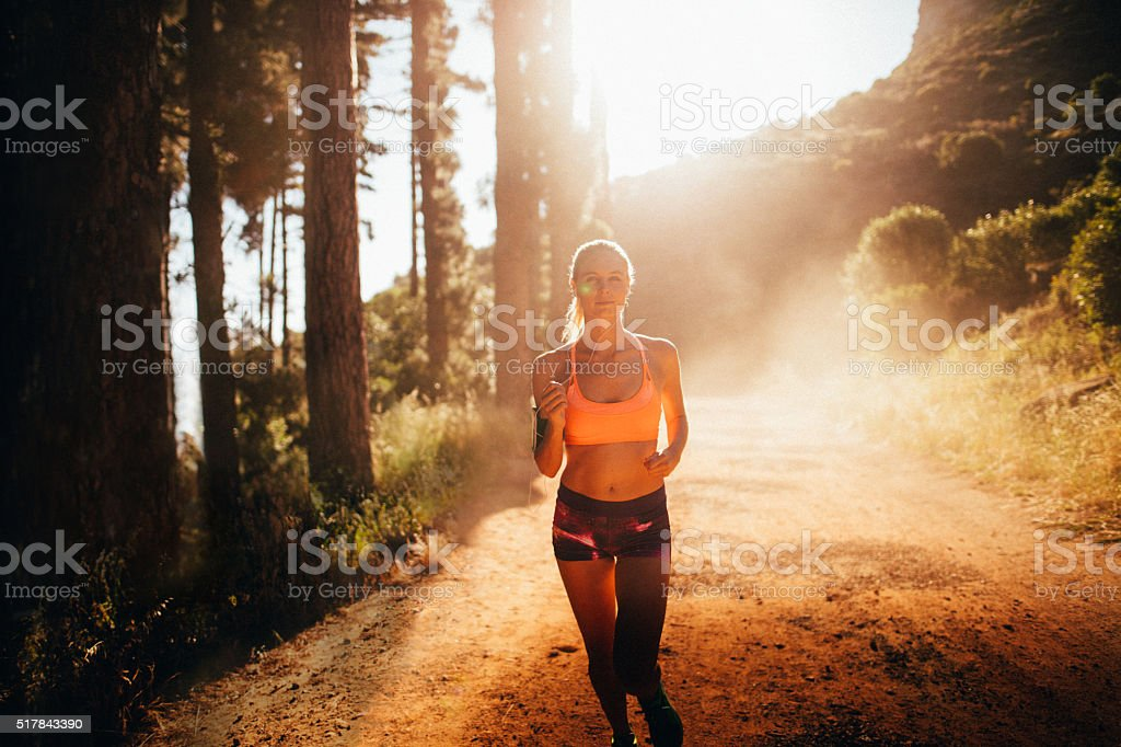 Fit athletic woman running on a sunlit mountain dirt path stock photo