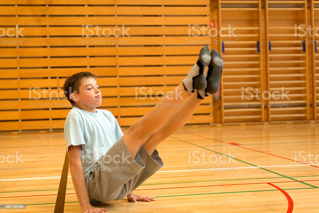 Eleven years old boy in t-shirt and gray shorts exsercising on the...