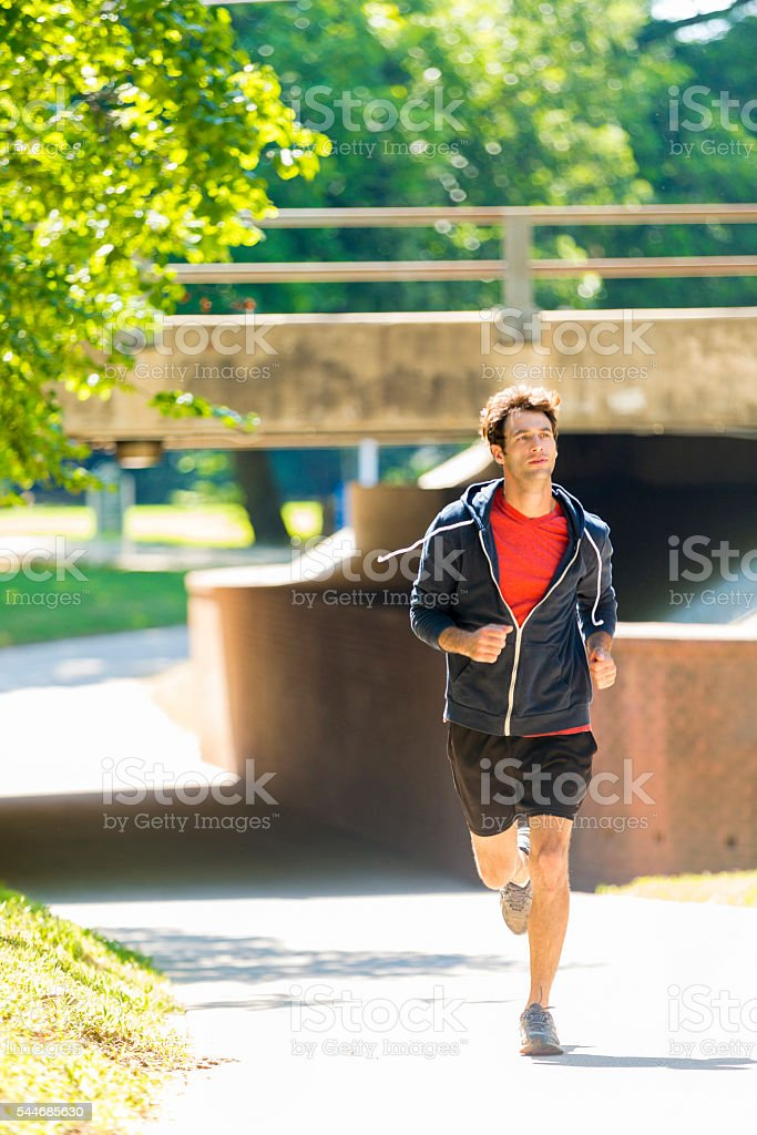Fit caucasian man running in a park stock photo