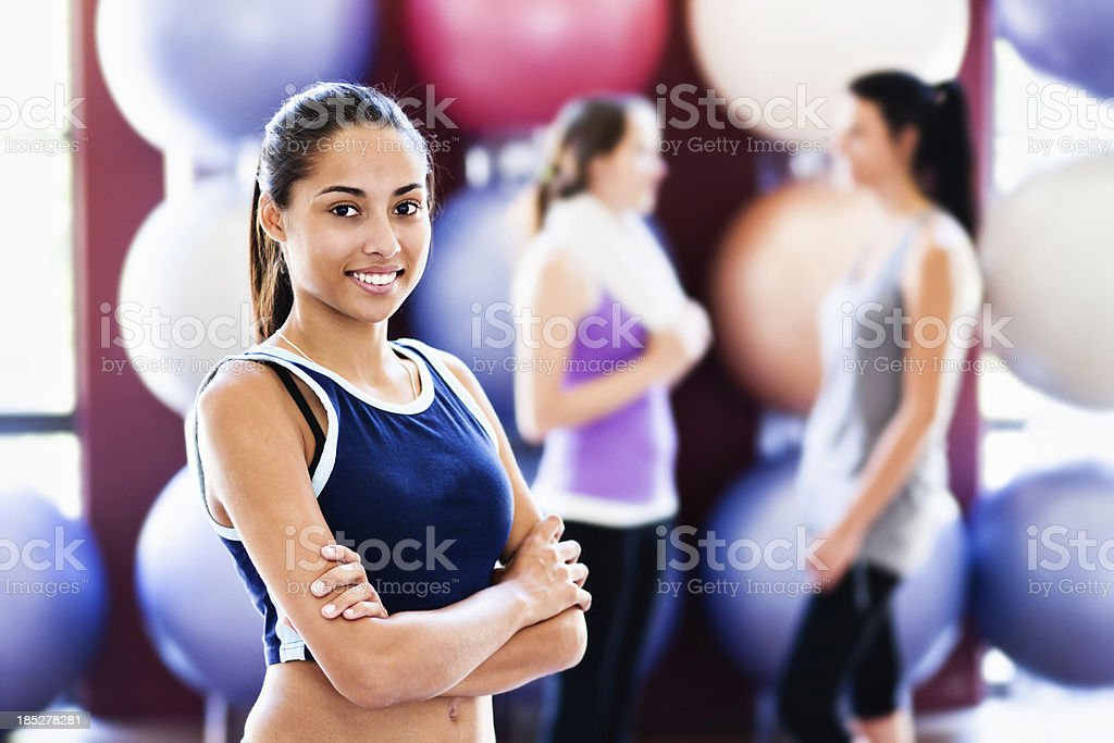 Fit confident young woman relaxes after exercising in gym stock photo
