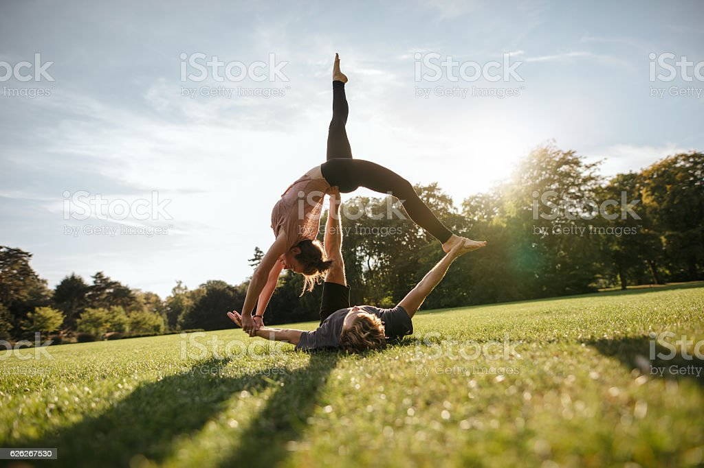 Fit couple doing acrobatic exercise in park stock photo