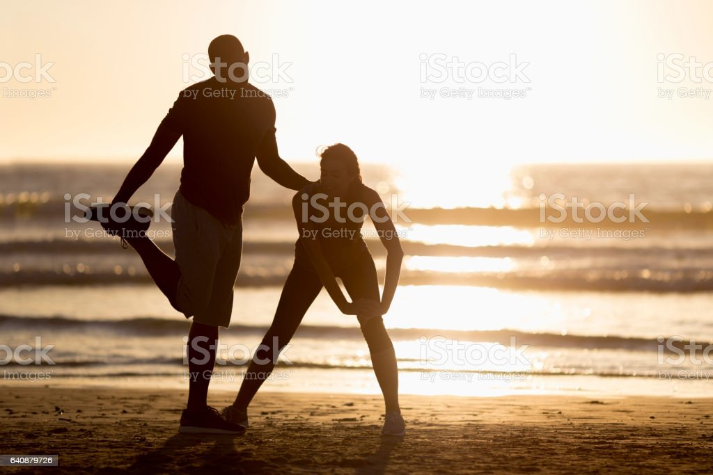 Fit couple exercising at beach during sunset stock photo