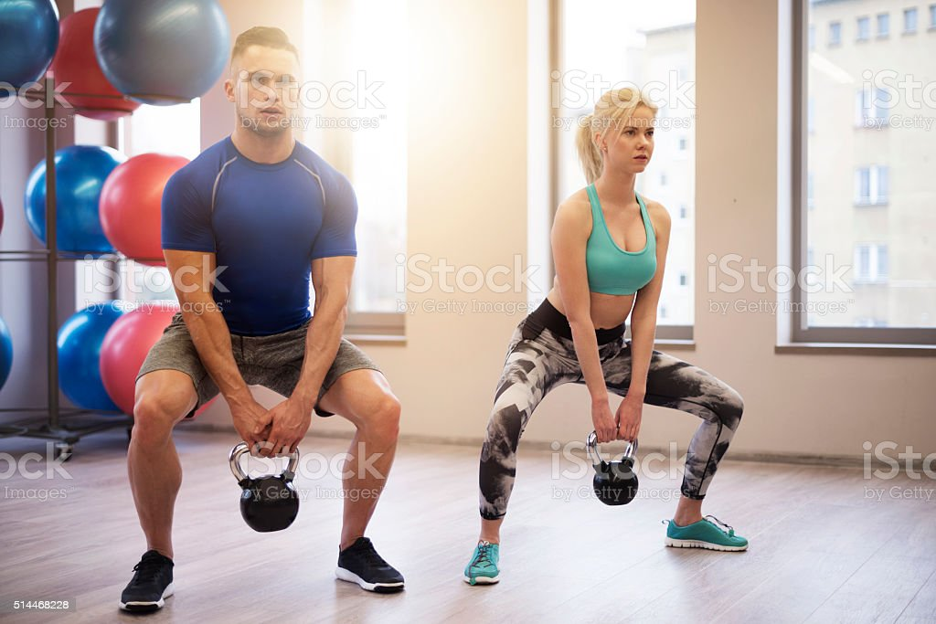 Fit couple lifting heavy kettles stock photo