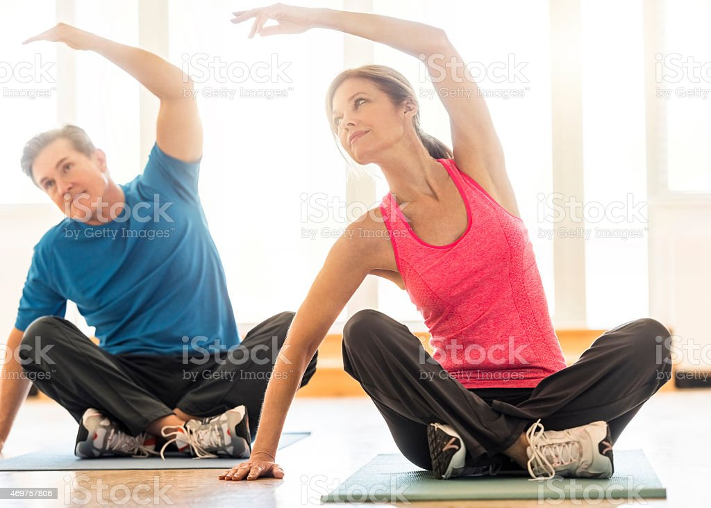Fit couple practicing yoga on mat at home stock photo