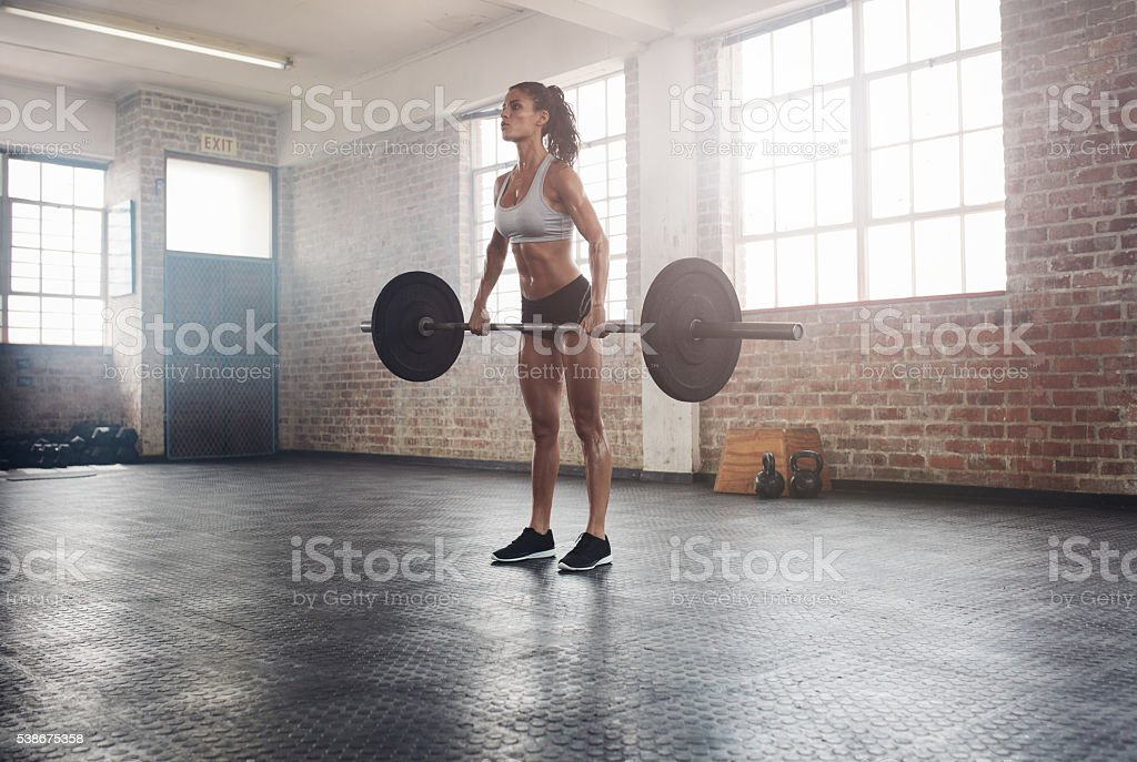 Fit female athlete lifting weights in gym stock photo