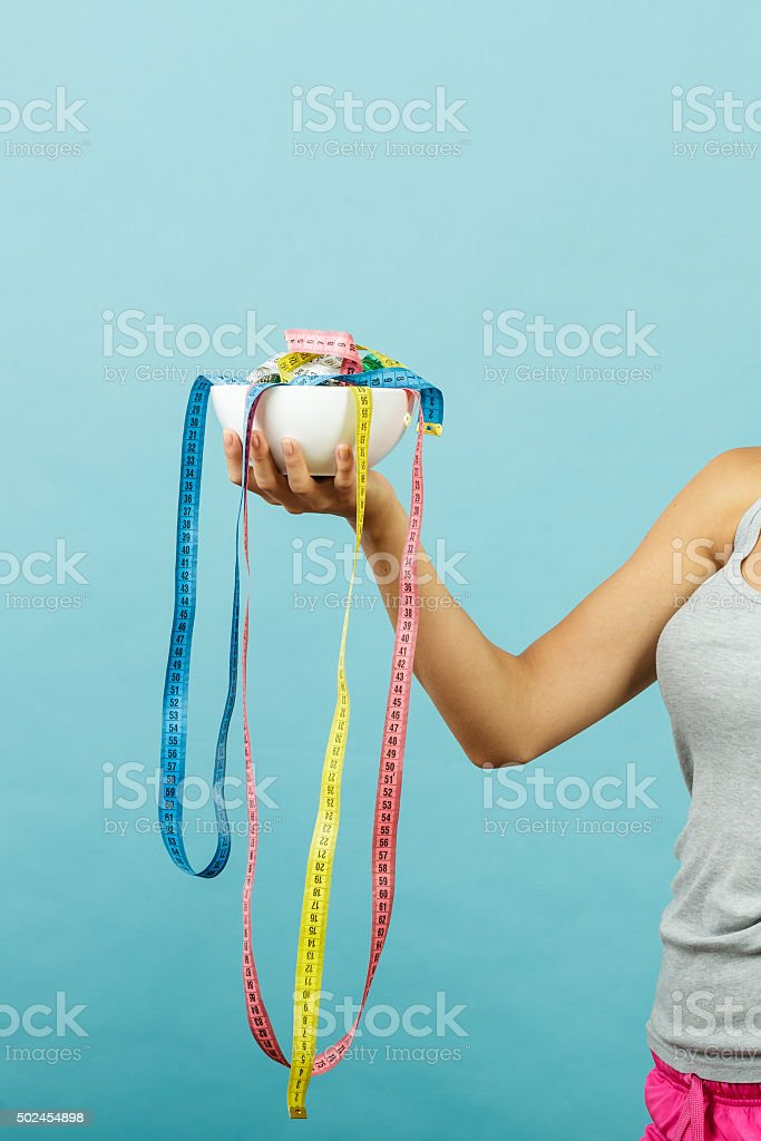 Fit girl holds bowl with many measuring tapes stock photo