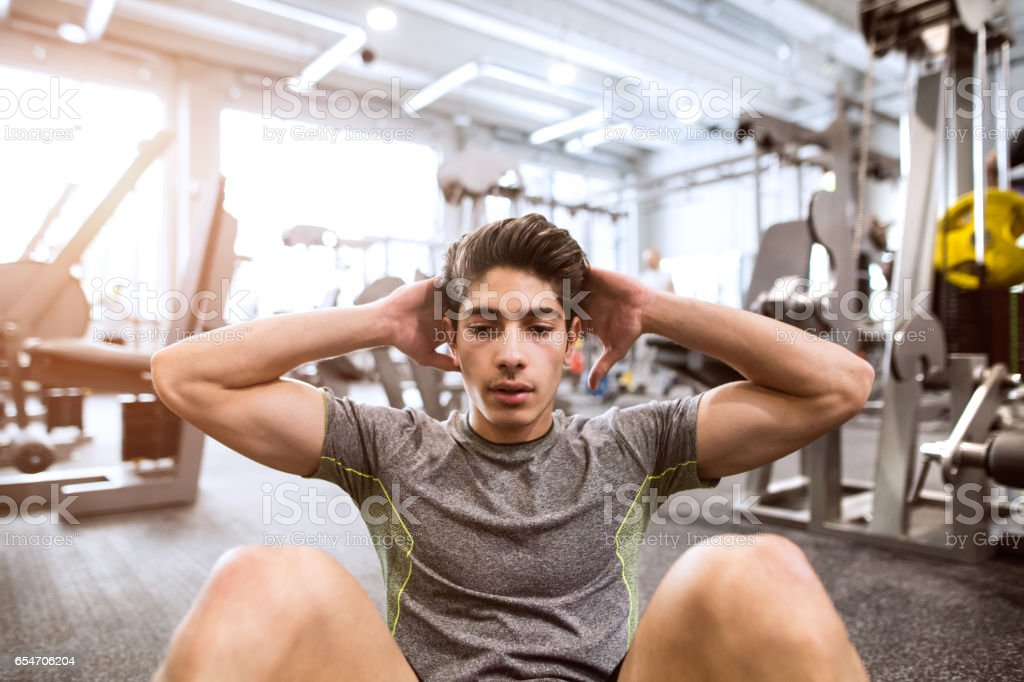 Fit hispanic man in gym training, working abs, doing crunches stock photo